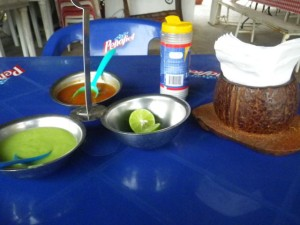 Mexican condiments: salt, lime, hot sauce, and guacamole (a very thin avocado-based sauce).